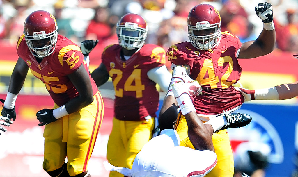 . Southern California linebacker Lamar Dawson (55) along with safety Demetrius Wright (24) and linebacker Devon Kennard (42) stop Boston College on a third down during the second half of an NCAA college football game in the Los Angeles Memorial Coliseum in Los Angeles, on Saturday, Sept. 14, 2013. Southern California won 35-7. 