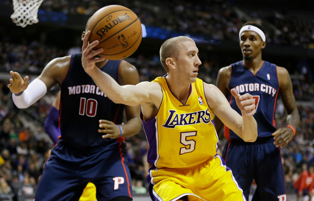 . Los Angeles Lakers guard Steve Blake (5) recovers the loose ball and looks to pass around Detroit Pistons forward Greg Monroe (10) and guard Brandon Jennings (7) during the second quarter of an NBA basketball game at the Palace in Auburn Hills, Mich., Friday, Nov. 29, 2013. (AP Photo/Carlos Osorio)