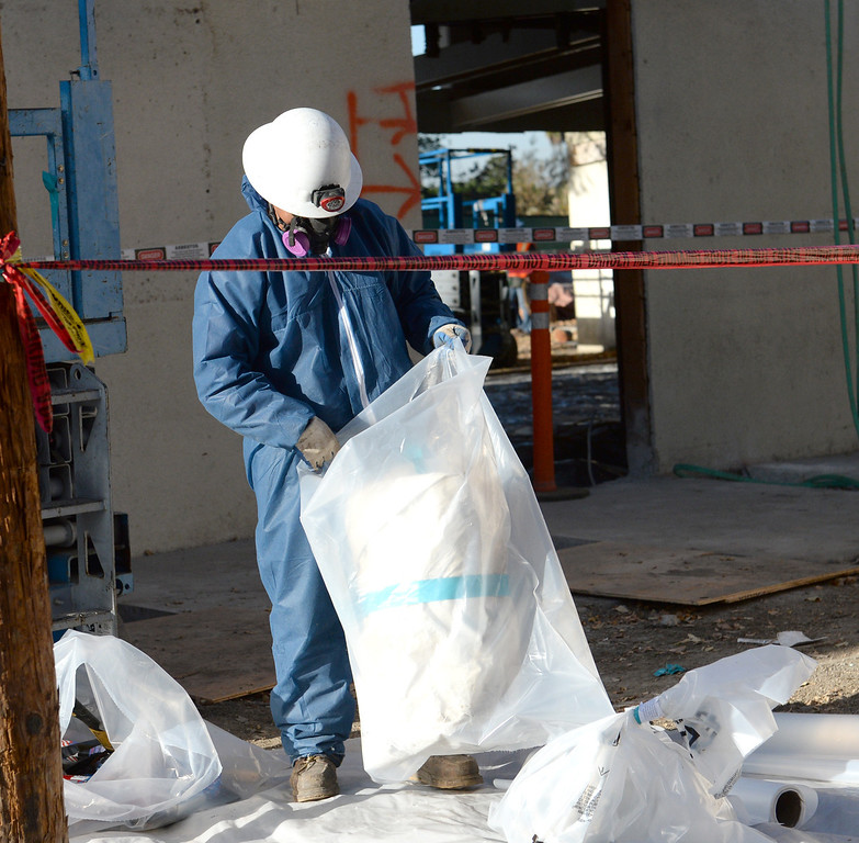 . Workers from Resource Environmental, Inc. package up Asbestos that being removed from La Habra Heights City Hall on Wednesday January 22, 2014. More asbestos was found in the roofing material last week. (Staff Photo by Keith Durflinger/Pasadena Star-News)