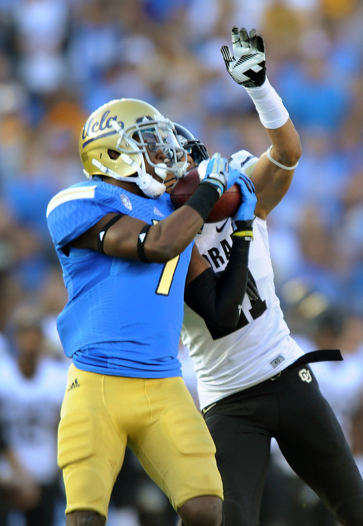 . UCLA WR Devin Fuller catches a pass for a 76-yard touchdown as Colorado\'s Jered Bell defends in the first quarter, Saturday, November 2, 2013, at the Rose Bowl. (Photo by Michael Owen Baker/L.A. Daily News)