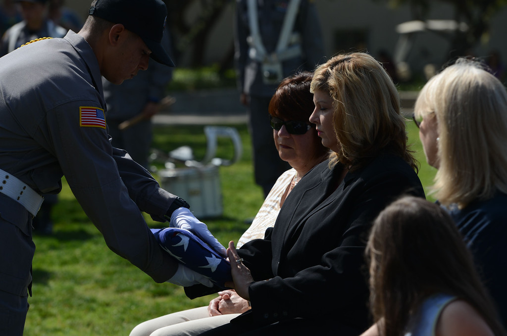 . Marci Daniels, director of CalState San Bernardino\'s Veterans Success Center, receives a folded flag that will be placed in the center\'s lobby. In recognition of Memorial Day, Cal State�s Student Veterans Organization and the Veterans Success Center pays tribute to fallen military service members, and former CalState student Alejo Thompson. Thompson was a U.S. Army 1st Lt. killed  last year in Parwan Province. Based at Fort Carson, Colo., he was assigned to the A Company, 1st Battalion, 12th Infantry Regiment, 4th Infantry Division. (Rick Sforza/Staff photographer, The Sun)