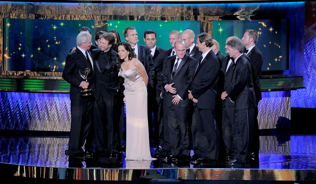 . From left, Bertram van Munster, Jerry Bruckheimer and Elise Doganieri are joined by the crew of The Amazing Race as they accept the award for outstanding reality competition program at the 63rd Primetime Emmy Awards on Sunday, Sept. 18, 2011 in Los Angeles. (AP Photo/Mark J. Terrill)