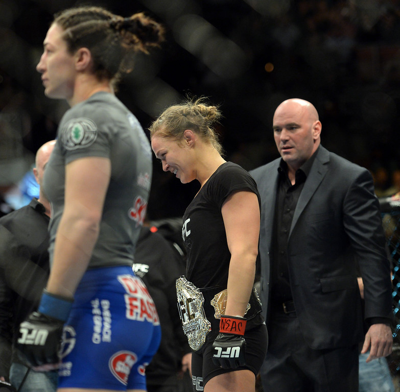 . UFC women\'s bantamweight champion Ronda Rousey lands a knee to the body of Sara McMann dropping her the the canvas during  UFC 170 at the Mandalay Bay Events Center in Las Vegas February 22, 2014. Rousey defeated McMann by referee stoppage in the first round. (Photo by Hans Gutknecht/Los Angeles Daily News)