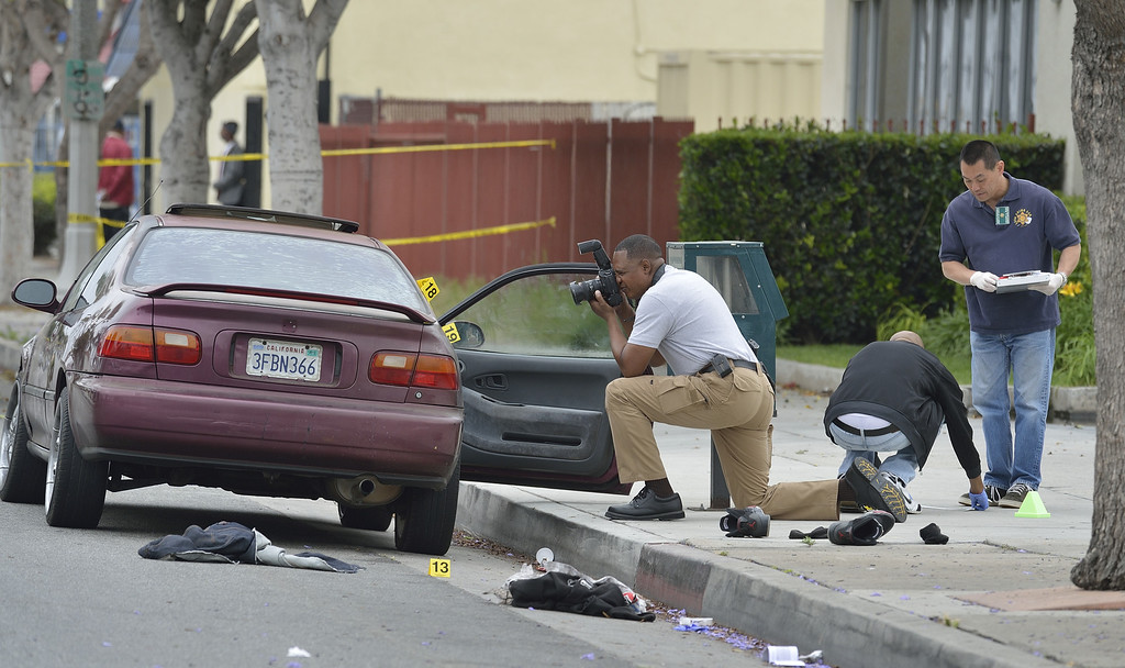 . COMPTON, CALIF. USA --  Los Angeles Sheriff investigators examine the 500  block of Long Beach Blvd. in Compton, Calif., on May 5, 2013, after an early morning shooting left one man dead and another man injured. Detectives were still at the scene Sunday afternoon.  No other details of the incident have been released. Photo by Jeff Gritchen / Los Angeles Newspaper Group