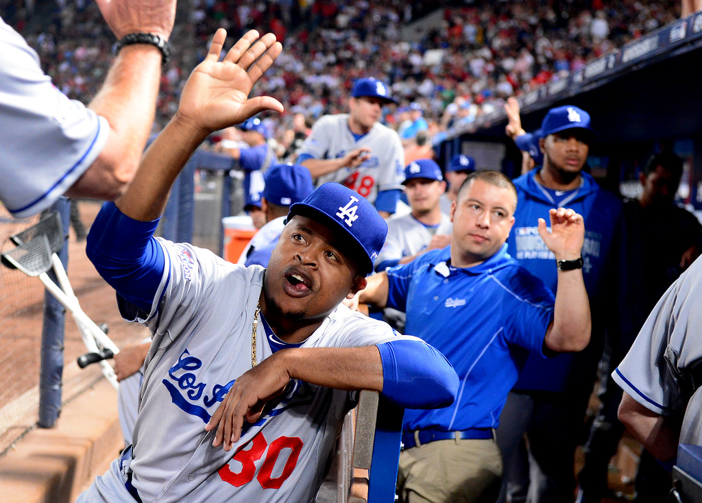 . Los Angeles Dodgers\' Edinson Volquez reaches out to his team from the bench as they defeat the Atlanta Braves 6-1 in the first game of the playoffs Thursday, October 3, 2013 at Turner Field in Atlanta, Georgia. (Photo by Sarah Reingewirtz/Pasadena Star- News)