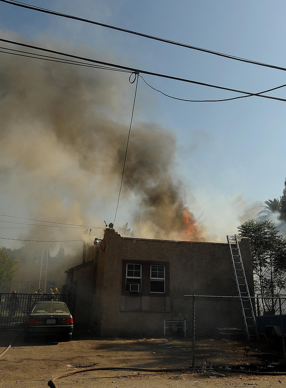 . Smoke billows from a residence burned by a four-alarm fire along the 700 block of Seventh Street in San Bernardino August 18, 2013. GABRIEL LUIS ACOSTA/STAFF PHOTOGRAPHER.