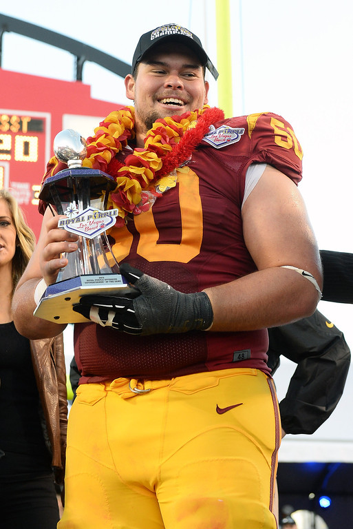 """. LAS VEGAS, NV - DECEMBER 21:  Abe Markowitz #50 of the USC Trojans holds the Offensive \""""Outperformer\"""" of the Game award after the team defeated the Fresno State Bulldogs 45-20 to win the Royal Purple Las Vegas Bowl at Sam Boyd Stadium on December 21, 2013 in Las Vegas, Nevada.  (Photo by Ethan Miller/Getty Images)"""