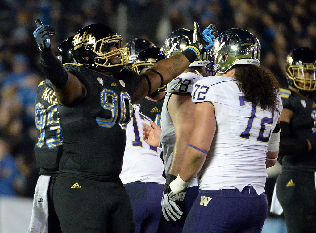 . UCLA Bruins\'s Ellis McCarthy (90) reacts after sacking Washington Huskies quarterback Keith Price ( not pictured) during the first half of their college football game in the Rose Bowl in Pasadena, Calif., on Friday, Nov. 15, 2013. 