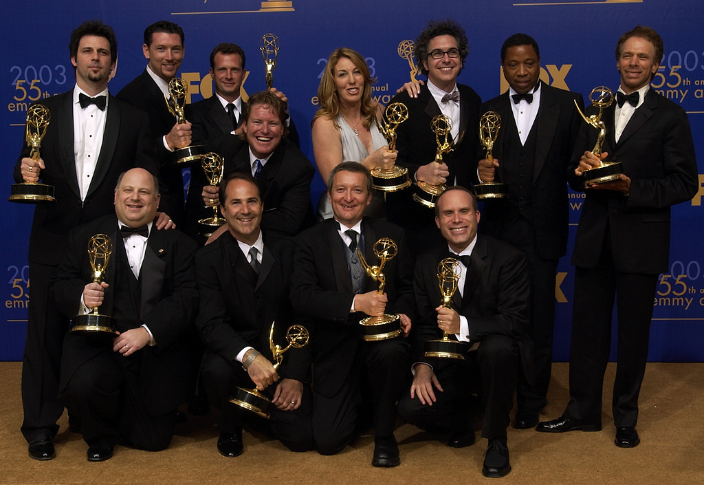 ". Jerry Bruckheimer, executive producer and creator of ""Amazing Race,\"" poses with producers from the show after they won the award for outstanding reality series at the 55th annual Primetime Emmy Awards Sunday, Sept. 21, 2003, in Los Angeles. (AP Photos/Reed Saxon)"
