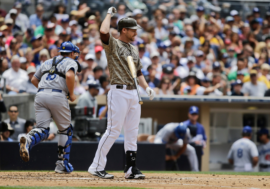 . San Diego Padres\' Chase Headley flips away his bat as Los Angeles Dodgers catcher Tim Federowicz heads for the dugout after Headley struck out to end the fourth inning of a baseball game in San Diego, Sunday, June 23, 2013. (AP Photo/Lenny Ignelzi)