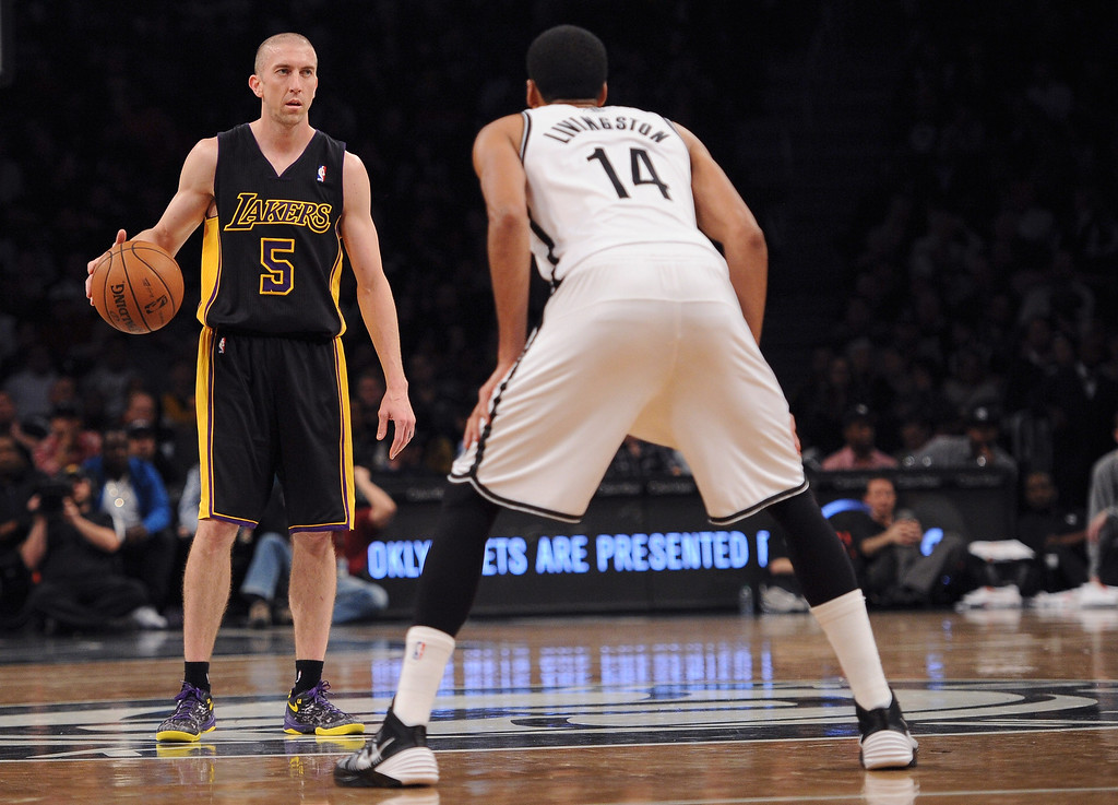 . Steve Blake #5 of the Los Angeles Lakers carries the ball downcourt with pressure from Shaun Livingston #14 of the Brooklyn Nets during the second quarter at Barclays Center on November 27, 2013 in the Brooklyn borough of New York City.   (Photo by Maddie Meyer/Getty Images)