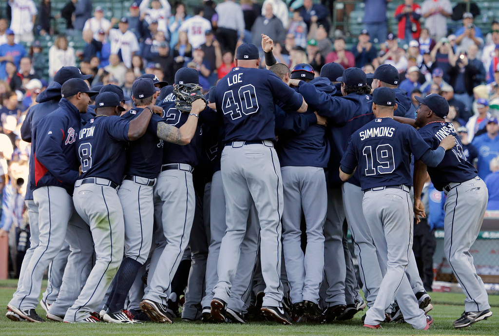 . Atlanta Braves players and coaches celebrate after the Braves defeated the Chicago Cubs 5-2 in a baseball game in Chicago, Sunday, Sept. 22, 2013. The Braves clinched the NL East as the Washington Nationals lose to the Florida Marlins. (AP Photo/Nam Y. Huh)
