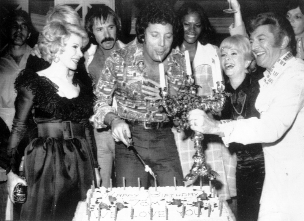 . British singer Tom Jones, centre, blows out candles at a surprise birthday party at Caesar\'s Palace, Las Vegas, June 6, 1974. Guests include, from left to right, Joan Rivers, Sonny Bono, Jones, Debbie Reynolds, and Liberace. (AP Photo)