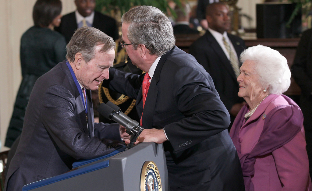 . Former Florida Gov. Jeb Bush, center, reaches to embrace his father, former President George H.W. Bush, left, who received the 2010 Medal of Freedom from President Barack Obama during a ceremony in the East Room of the White House in Washington, Tuesday, Feb. 15, 2011. At right former first lady Barbara Bush. (AP Photo/Pablo Martinez Monsivais)