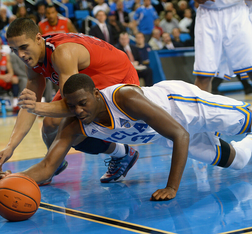 . UCLA\'s Jordan Adams and Arizona\'s Nick Johnson dive for a loose ball along the baseline, Thursday, January 9, 2014, at Pauley Pavilion. (Photo by Michael Owen Baker/L.A. Daily News)