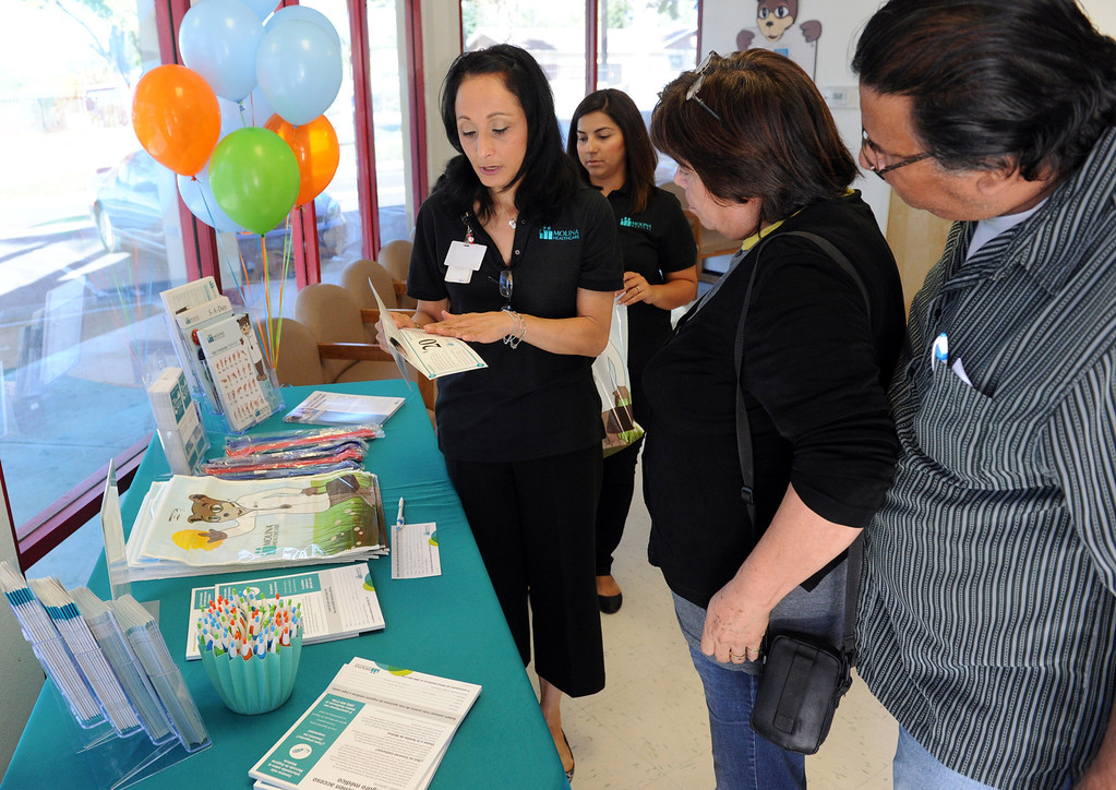 . (John Valenzuela/Staff Photographer) Victor and Alicia Gomez of Ontario recieves information about health insurance with Covered California from Joann Schmidt, community outreach coordinator for Molina Medical at Molina Medical in Fontana, Tuesday, Oct. 1, 2013. Today kick off the first day of open enrollment for Covered CA, the marketplace for affordable, private health insurance, Molina Medical  hosted an informational event for its patients and the Inland Empire community.