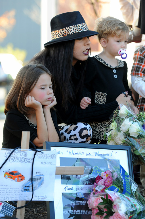 . Angel Princess sits with her nieces Skyler Presley, 6, left, and Riley Presley, 2, at a memorial for Paul Walker and Roger Rodas, Sunday, December 1, 2013, at the scene of their fatal crash site on Hercules Street near Kelly Johnson Parkway in Valencia. (Photo by Michael Owen Baker/L.A. Daily News)