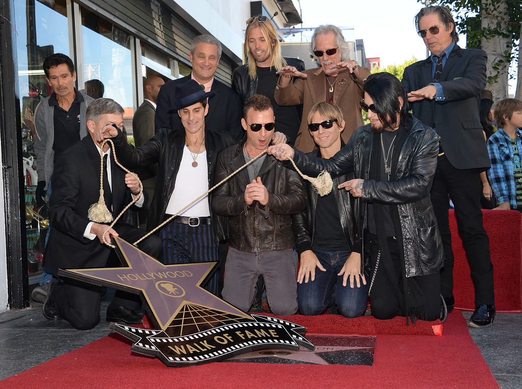 . From left: Perry Farrell, Stephen Perkins, Chris Chaney and Dave Navarro of the alt-rock band Jane\'s Addiction react as their star is unveiled at the ceremony honoring the band with a star on The Hollywood Walk of Fame, October 30, 2013 in Hollywood, California.  In the back row are Taylor Hawkins of the Foo Fighters, John Densmore of The Doors and John Doe from X.           (ROBYN BECK/AFP/Getty Images)
