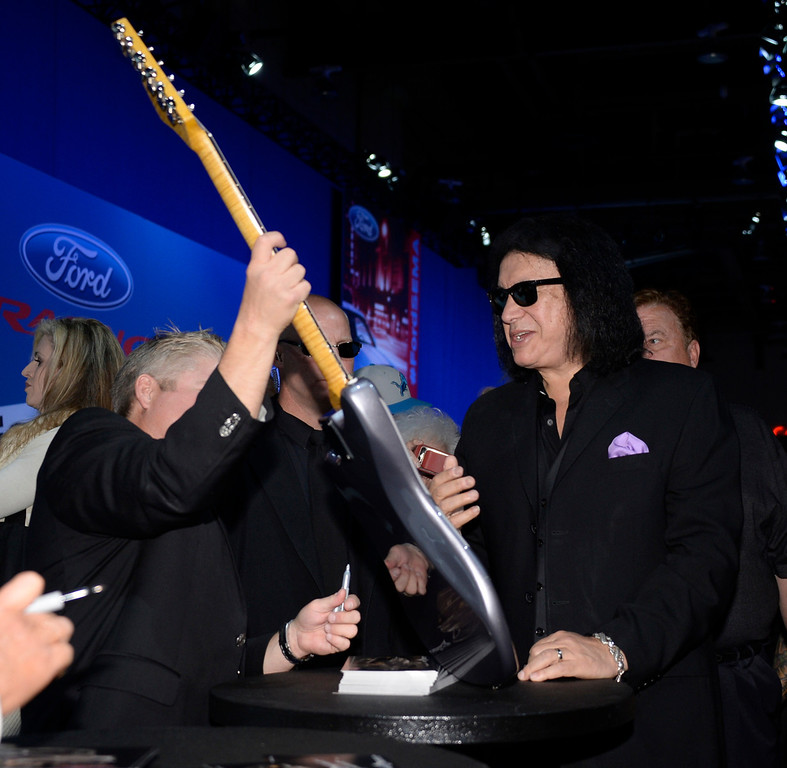 . Nov 5,2013 Las Vegas NV. USA. KISS front man Gene Simmons signs a guitar that will go with a customized 1956 F-100 pickup, to be auctioned off for charity in Jan 2014 at the 2014 Barrett-Jackson Auction in AZ,  during the first day of the 2013 SEMA auto show.