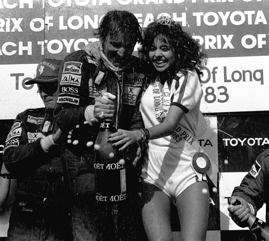 . John Watson of Great Britain and Long Beach Grand Prix Queen Karen Mistal get soaked by champagne in the winner\'s circle after the race March 28, 1983. Watson, driving a McLaren-Ford, came from 22nd position in a 26-car field to win the race. Watson\'s teammate, Niki Lauda, who finished second, is at left. (AP Photo/Doug Pizac)