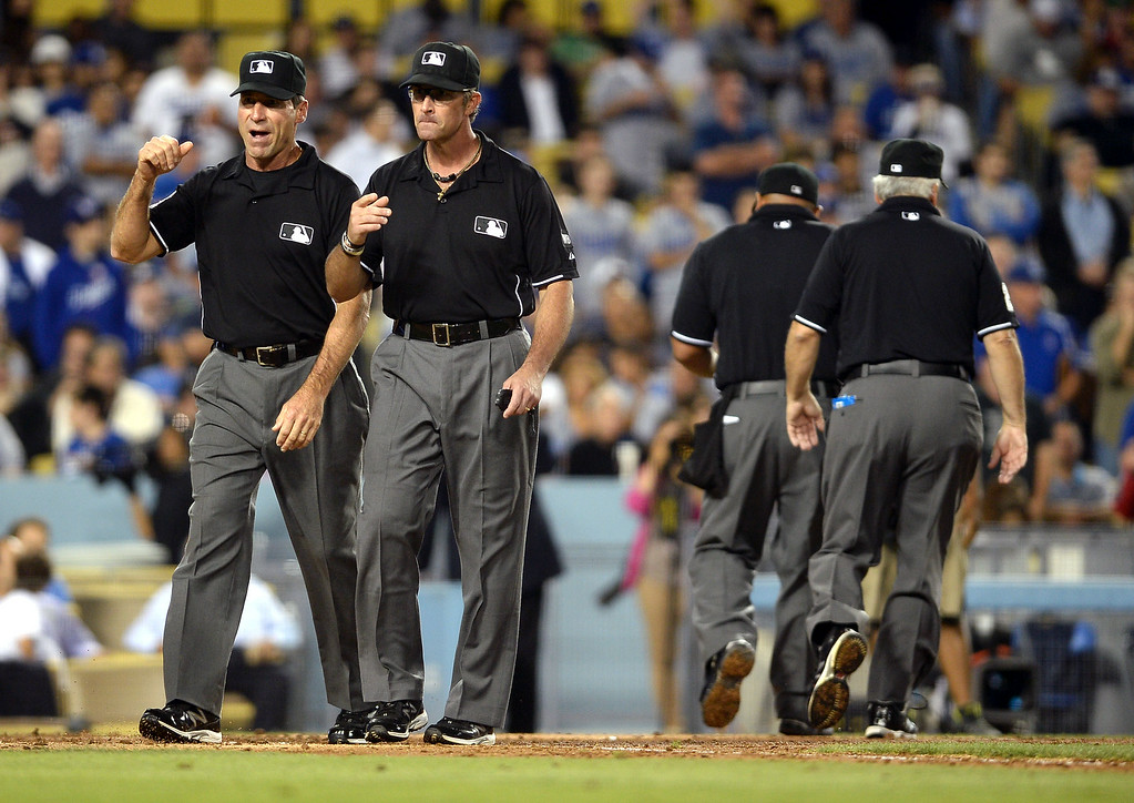 . Umpires gather to review a triple play against the Los Angeles Dodgers July 1, 2014 in Los Angeles.(Andy Holzman/Los Angeles Daily News)