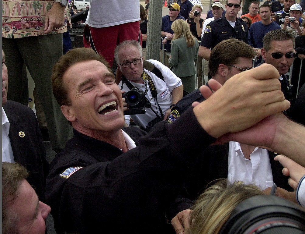 . 10/6/03 - Arnold Schwarzenegger candidate for California Governer shakes hands with supporters at the Hungtington Beach Pier, a ralley the day before the recall election.Photo by David Waters/For the Press-Telegram