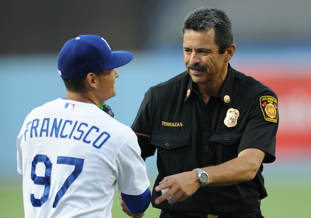 . Newly installed LAFD Chief Ralph Terrazas is congratulated by Francisco Herrera after he threw out the first pitch at Dodger Stadium, as the team hosts the San Diego Padres at the inaugural Firefighter Appreciation Night. Los Angeles, CA. 8/19/2014(Photo by John McCoy Daily News)