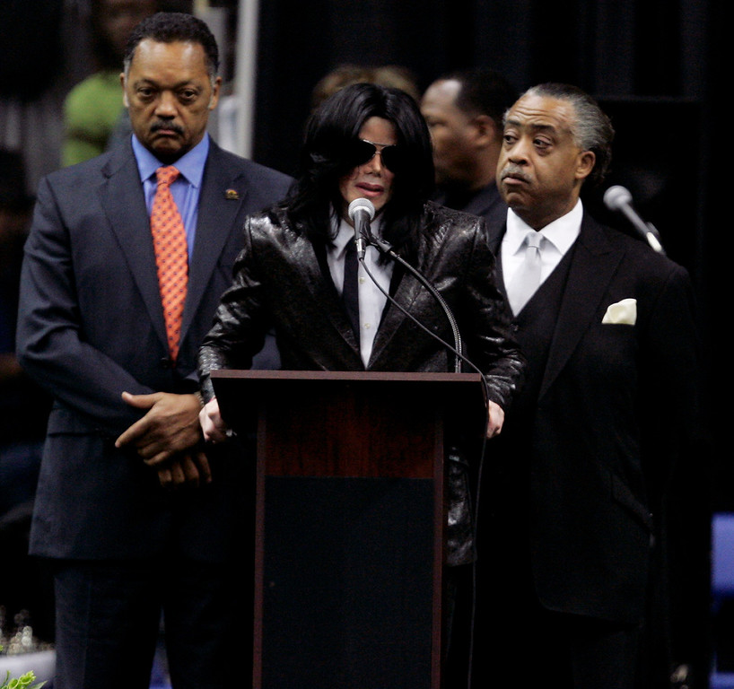 . Michael Jackson speaks at the podium, flanked by Rev. Jesse Jackson, left, and Rev. Al Sharpton, during the funeral service for singer James Brown at the James Brown arena in Augusta, Ga., Saturday, Dec. 30, 2006. (AP Photo/John Bazemore)