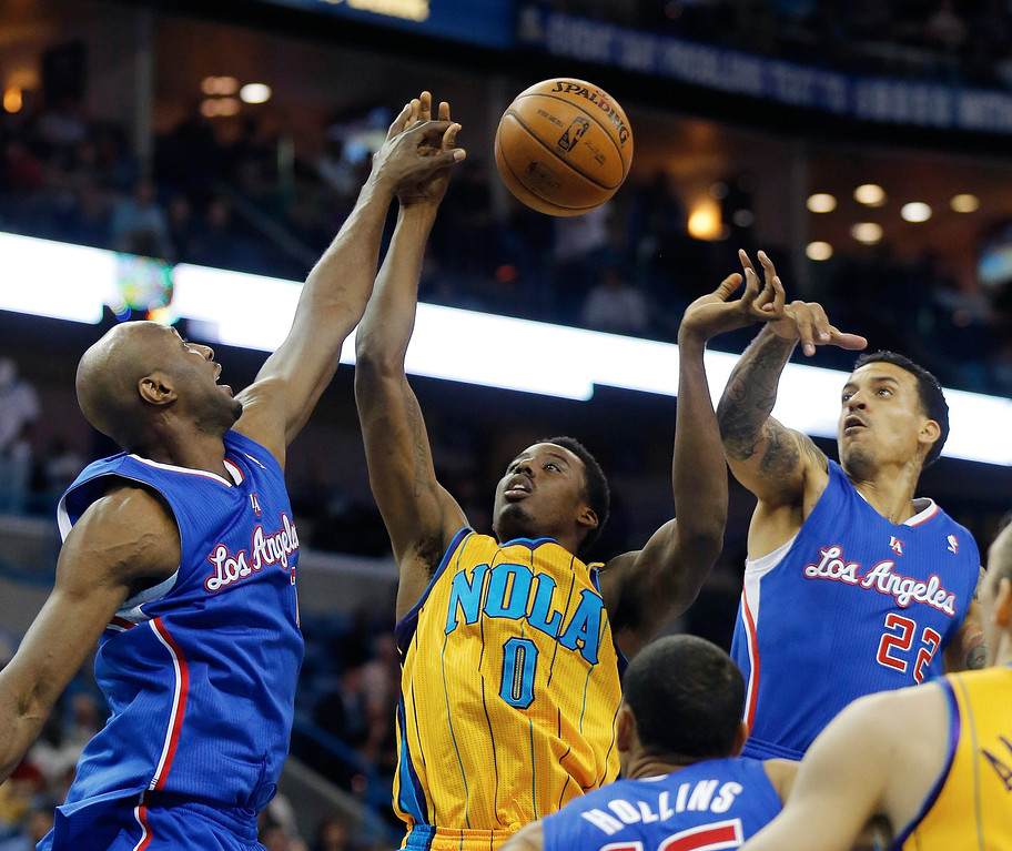 . Los Angeles Clippers forward Lamar Odom (7) hits the hand of New Orleans Hornets forward Al-Farouq Aminu (0) as Clippers forward Matt Barnes (22) reaches in during the first half of an NBA basketball game, Friday, April 12, 2013, in New Orleans.  (AP Photo/Bill Haber)