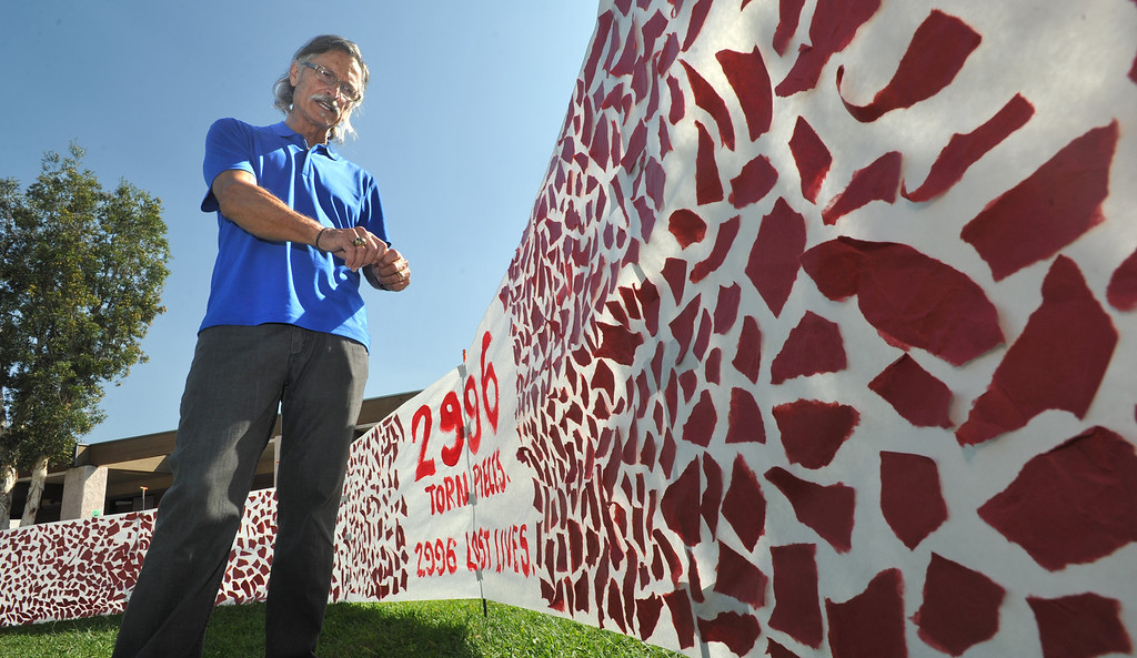 . Art teacher Dave Hamel shows their 9/11 display with a 75-foot banner of torn pieces of paper in the quad at Diamond Bar High School in Diamond Bar, CA on Wednesday September 11, 2013.  The annual tribute includes paper mache� replicas of the Twin Towers and Pentagon. (San Gabriel Valley Tribune/Staff Photo by Keith Durflinger)