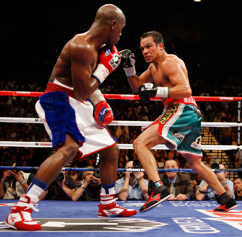 . Juan Manuel Marquez, right, of Mexico, charges at Floyd Mayweather Jr., during their non-title welterweight boxing match in Las Vegas, Sunday, Sept. 20, 2009. (AP Photo/Rick Bowmer)