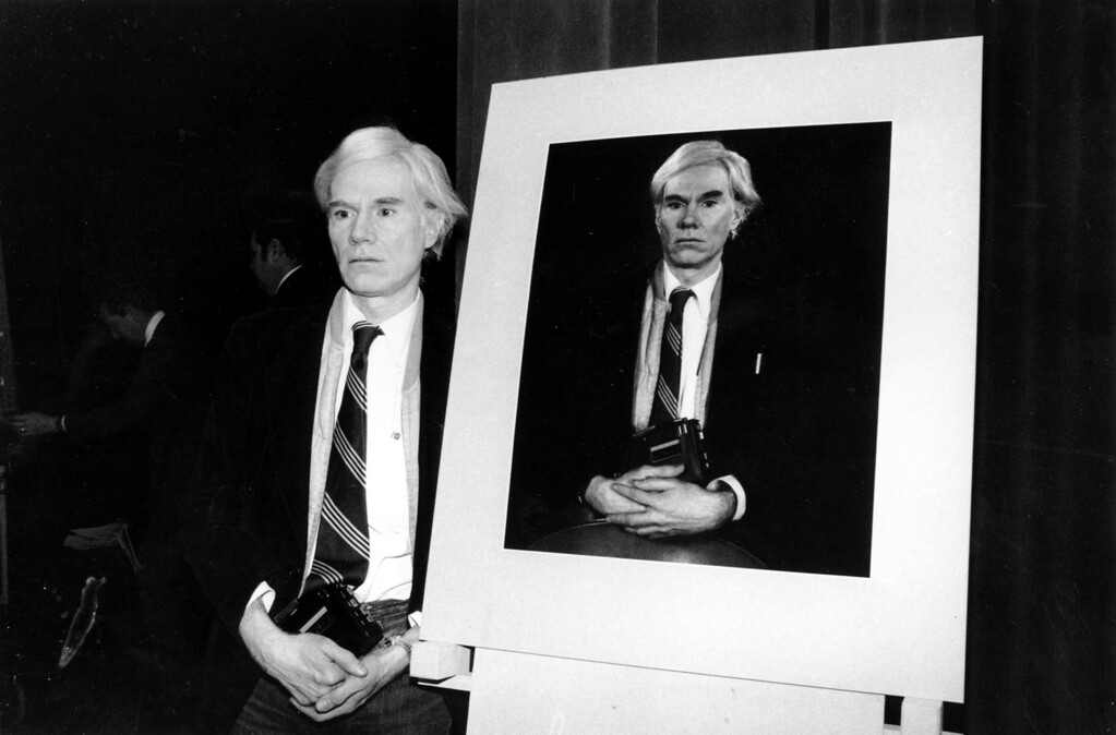 . Pop artist Andy Warhol, who often works with instant cameras, stands beside a portrait of himself taken with a Polaroid camera using 20x24 inch format film. Warhol is at a demonstration of new Polaroid products at the Waldorf Astoria Hotel in New York City on Jan. 31, 1978. He is holding a small tape recorder in his hands. (AP Photo)