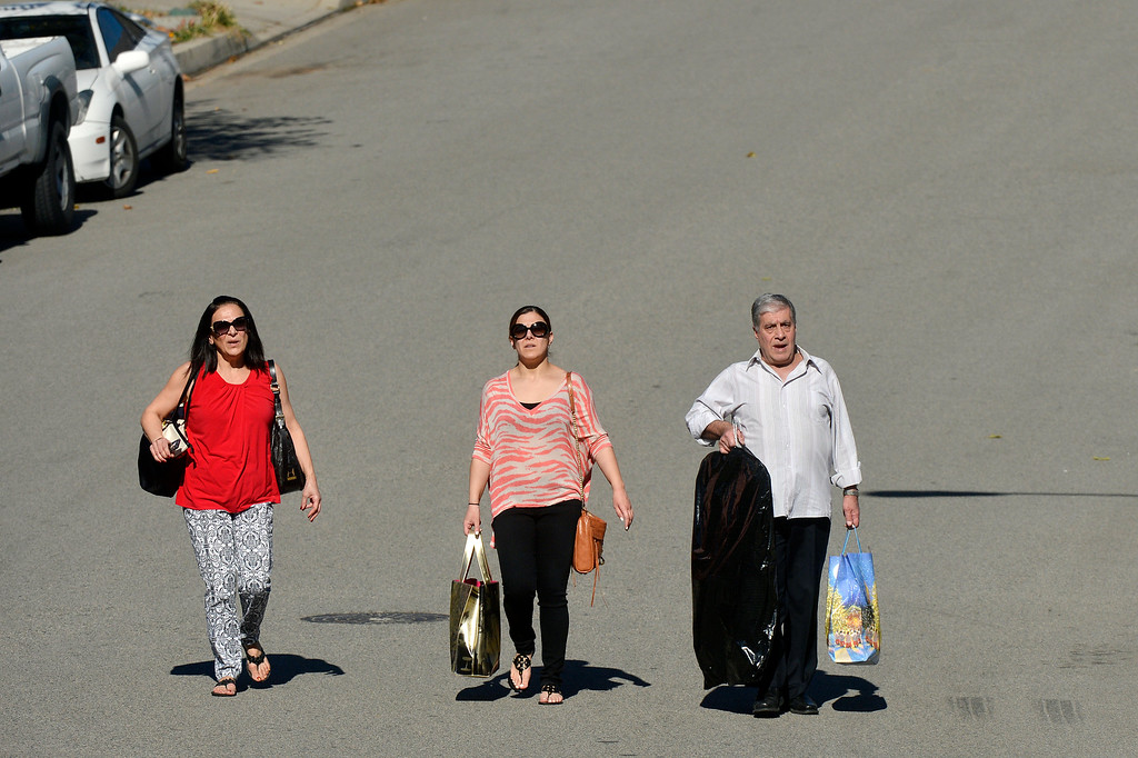 . Aida Chammas (left) and her husband Victor (right) walk down Nob Hill Drive in Azusa with their daughter Sandy (center) after retrieving clothing from their home Friday. The Chammas\' planned to stay with relatives Friday night since their area was still under evacuations. Clean up efforts were underway Friday January 17, 2014 in Glendora and Azusa following the Colby Fire. Full containment is expected by Sunday. (Will Lester/Inland Valley Daily Bulletin)
