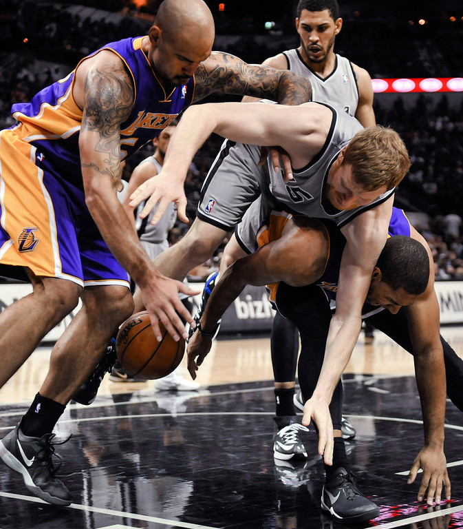 . San Antonio Spurs center Matt Bonner dives for a loose ball between Los Angeles Lakers players Robert Sacre, left, and Xavier Henry in the second half of an NBA basketball game Friday, March 14, 2014, in San Antonio. (AP Photo/Bahram Mark Sobhani)