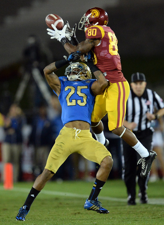 . USC�s De\'Von Flournoy #80 makes a catch over UCLA�s Damien Thigpen #25 but lands out of bounds for an incomplete pass during their game at the Los Angeles Memorial Coliseum Saturday, November 30, 2013.  UCLA beat USC 35-14. (Photo by Hans Gutknecht/Los Angeles Daily News)