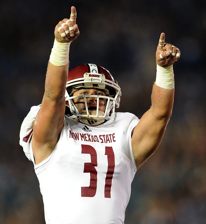 . New Mexico State safety Davis Cazares (31) points to the stands after intercepting a UCLA pass during the first half of their college football game in the Rose Bowl in Pasadena, Calif., on Saturday, Sept. 21, 2013.   (Keith Birmingham Pasadena Star-News)