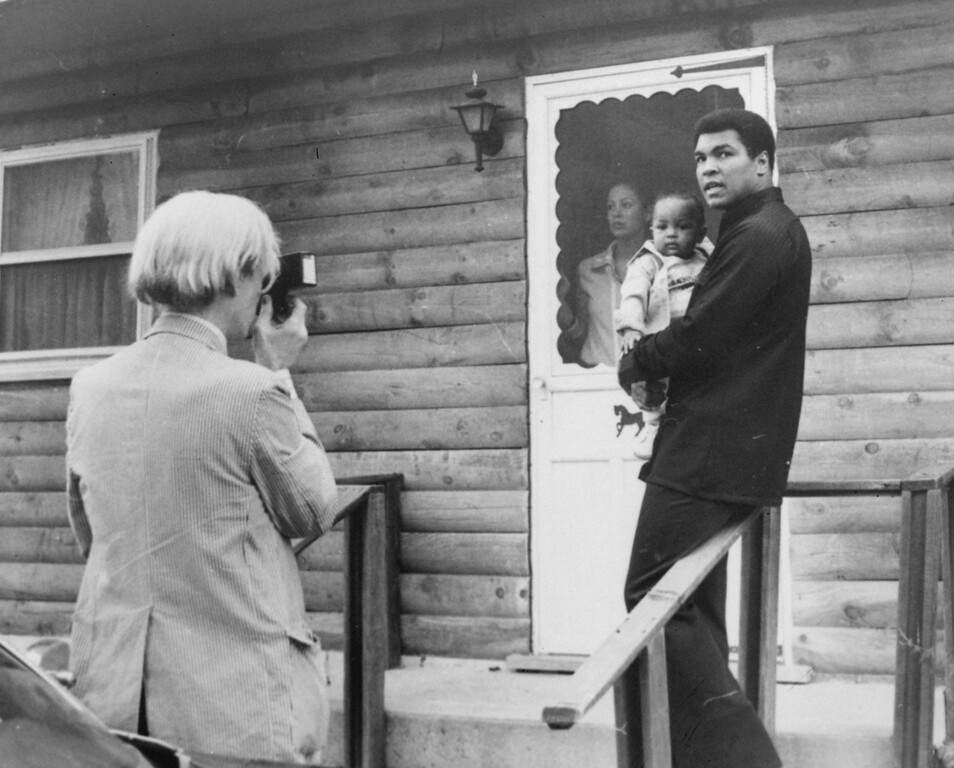 . Pop artist Andy Warhol, left, is shown photographing Muhammad Ali, his infant daughter, Hanna, and wife, Veronica, Thursday, August 18, 1977, at Ali\'s training camp in Deer Lake, Pa. (AP Photo)