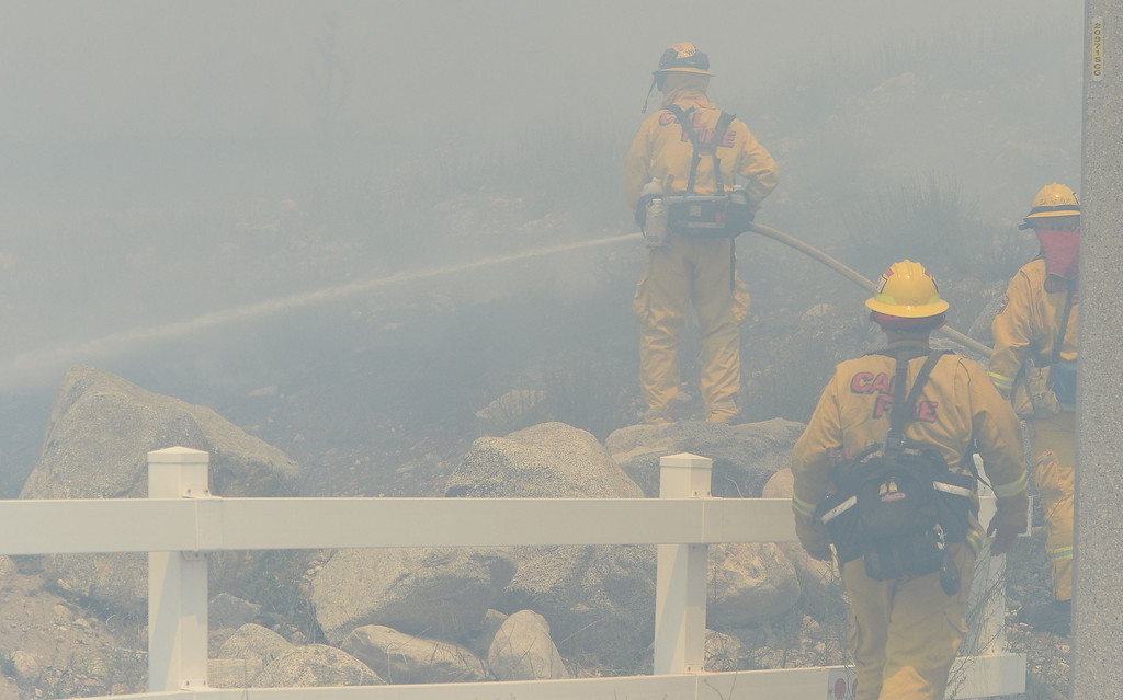 . Firefighters put out a spot fire Wednesday during the Etiwanda Fire Wednesday in Rancho Cucamonga. Over 1,000 acres and over a 1,000 homes are under mandatory evacuation as the Etiwanda Fire burns in Rancho Cucamonga Wednesday April 30, 2014. Cause of the fire is unknown and is burning in areas which burned during the Grand Prix Fire in October 2003. (Will Lester/Inland Valley Daily Bulletin)