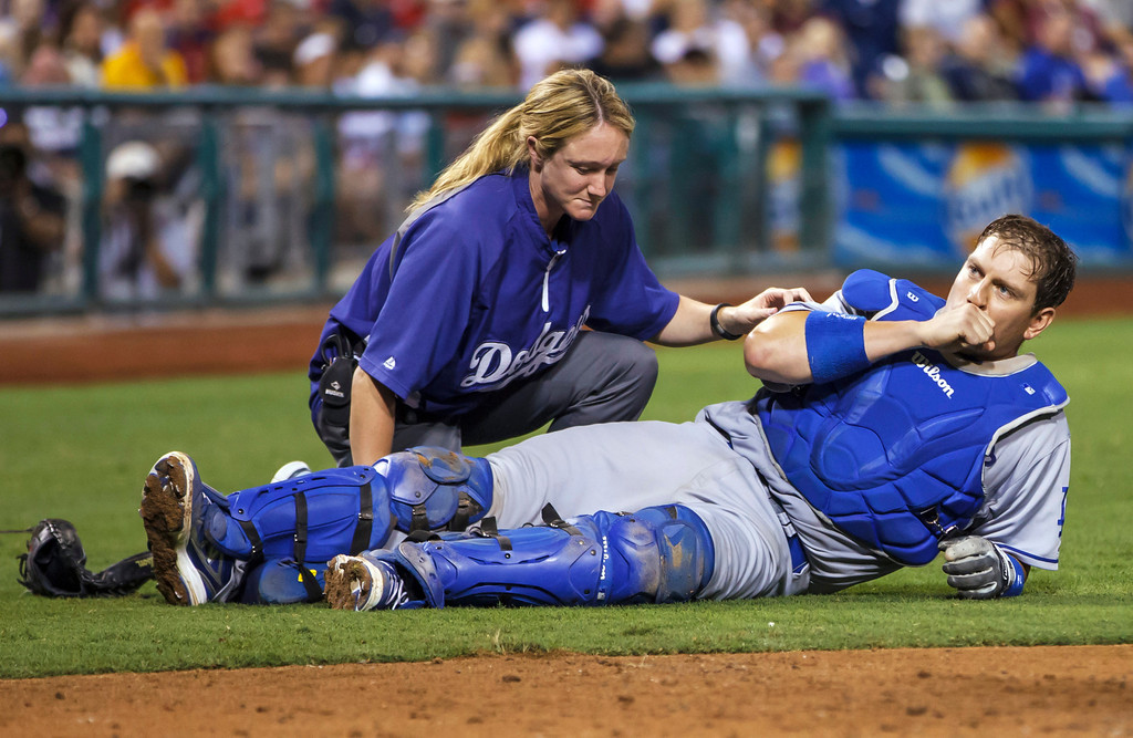 . Los Angeles Dodgers catcher A.J. Ellis is checked by trainer Sue Falsone after taking foul ball to the knee from Philadelphia Phillies\' Darin Ruf during the eighth inning of a baseball game, Friday, Aug. 16, 2013, in Philadelphia. The Dodgers won 4-0. (AP Photo/Christopher Szagola)