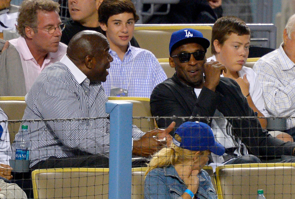""". Los Angeles Dodgers co-owner and former Los Angeles Laker Earvin \""""Magic\"""" Johnson, left, talks with Los Angeles Lakers\' Kobe Bryant as they watch the Dodgers play the New York Yankees in a baseball game, Wednesday, July 31, 2013, in Los Angeles. (AP Photo/Mark J. Terrill)"""