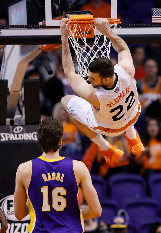 . Phoenix Suns\' Miles Plumlee (22) hangs from the rim after dunking as Los Angeles Lakers\' Pau Gasol (16), of Spain, watches during the first half of an NBA basketball game Wednesday, Jan. 15, 2014, in Phoenix. (AP Photo/Ross D. Franklin)
