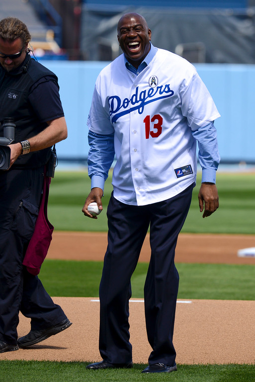 . Magic Johnson laughs after he is pulled from making the opening pitch at opening day at Dodger Stadium Monday.  Sandy Kofax relieved Magic to make the pitch. Photo by David Crane/Los Angeles Daily News.