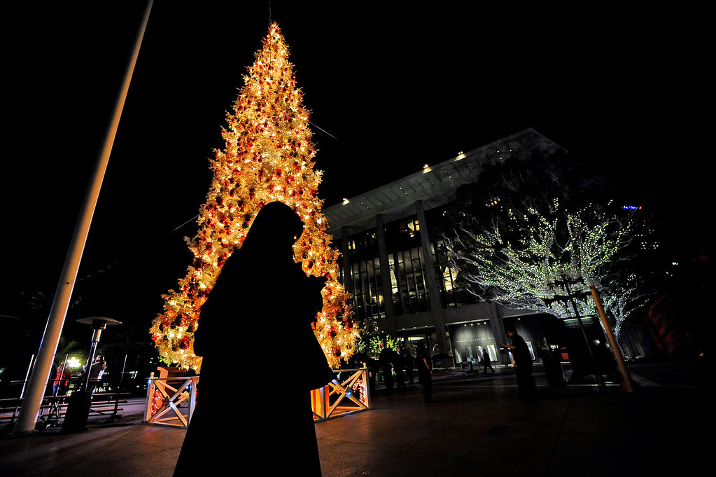 . A visitor passes by the Los Angeles County Christmas Tree following the annual lighting ceremony December 2 , 2013 in Los Angeles, CA.  The 50-foot tree is located in front of the  Los Angeles County Music Center in downtown Los Angeles.(Andy Holzman/Los Angeles Daily News)