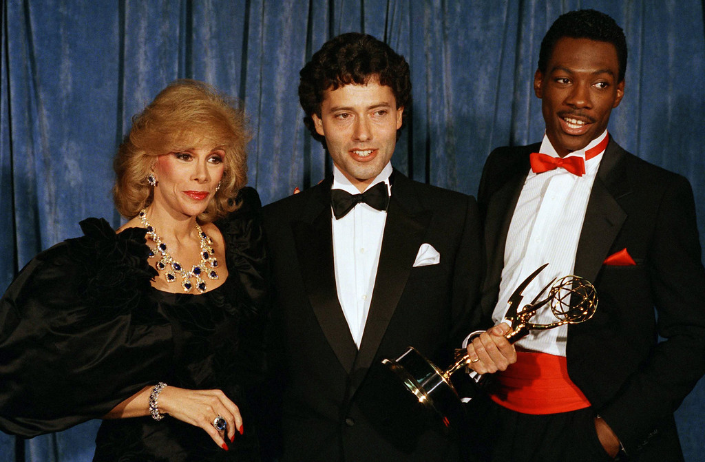 . Emmy Awards hosts Comedienne Joan Rivers, left, and comedian Eddie Murphy, right, during the Emmy awards in Pasadena, Sept. 23, 1984.  Man at center is unidentified. (AP Photo)