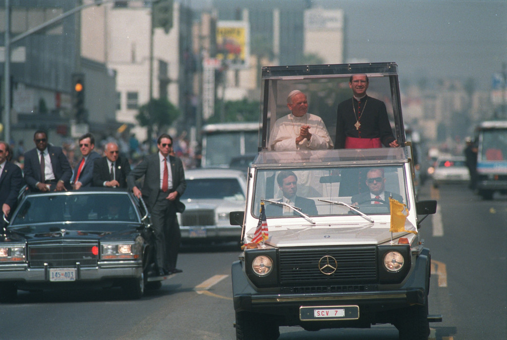 ". Pope John Paul II rides in his ""Popemobile\"" with Los Angeles Archbishop Roger Mahoney during a visit to Los Angeles in September 1987. (Los Angeles Daily News file photo)"