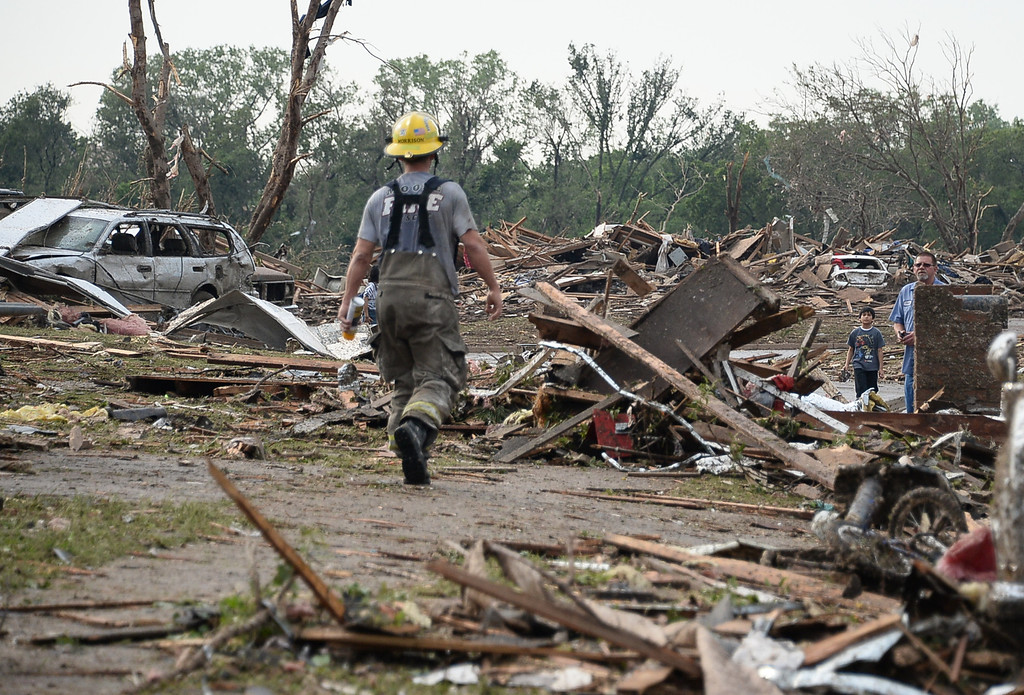 . A firefighters looks for victims among the destroyed buildings and overturned cars.