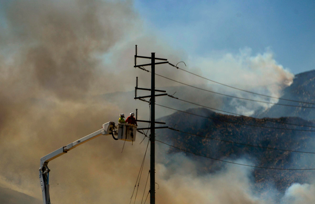 . Electrical crews work on the power lines along W. Lincoln Street as the Silver Fire burns in the mountains south of Banning August 8, 2013.   GABRIEL LUIS ACOSTA/STAFF PHOTOGRAPHER.