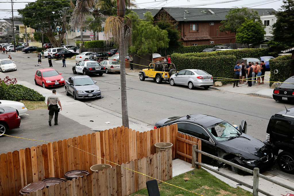. A deputy sheriff walks near a black BMW sedan driven by a drive-by shooter on Saturday, May 24, 2014, in Isla Vista, Calif. The shooter went on a rampage near a Santa Barbara university campus that left seven people dead, including the attacker, and seven others wounded, authorities said Saturday. (AP Photo/Jae C. Hong)