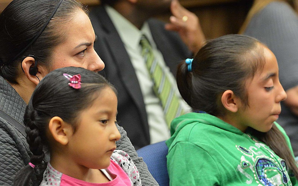 . Anna Gonzalez sits with her children as she listens to speakers during an emergency board meeting at the Rialto Unified School District. Gonzalez\'s daughter Oyuky Barragan is an eight grade student who did the Holocaust essay. For the first time since news broke of a controversial Holocaust essay assignment, the Rialto Unified School District School Board Wednesday night took �full responsibility� for the task, telling a packed board chamber that it was �horribly inappropriate.� (Photo by Rick Sforza/The Sun)