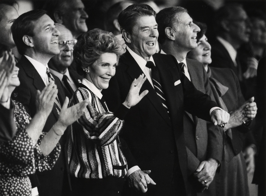 . 11/3/86 - At campaign pep rally held at Orange County Fairgrounds Amphitheater. Left to right- Senate candidate Ed Zschau with Nancy Reagan waving to fans- Pres. Ronald Reagan laughing and Gov. George Deukmejian. The groupwas having a good time watching the carnival of events at the close of the campaign rally. (File photo)